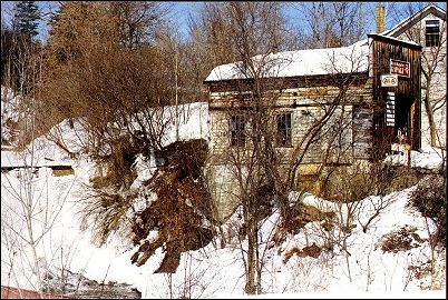 old mill building over frozen waterfall in spring